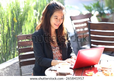 A portrait of a Young businesswoman work outdoor, in a cafe - stock photo