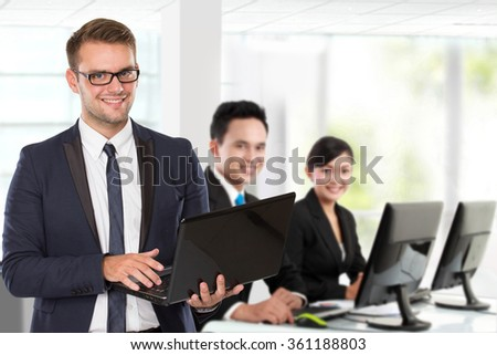 A portrait of a young caucasian businessman, with his team behind holding laptop. isolated in white background - stock photo