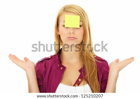 A portrait of a young confused woman with a sticky note on her forehead - stock photo