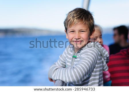 A portrait of a young happy boy wearing a striped hoodie on a boat or ferry ride - stock photo