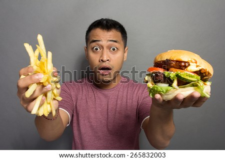 A portrait of a young man surprised with the size of his burger portion package - stock photo