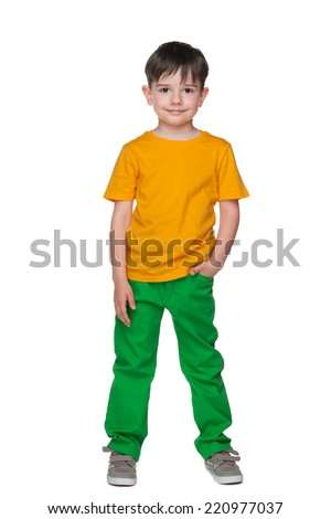 A portrait of a young smiling boy in a yellow shirt on the white background - stock photo