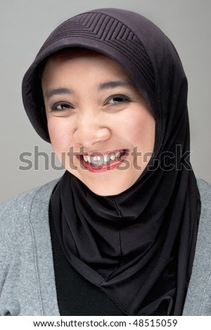 A portrait of a young smiling practising muslim woman in traditional head covering - stock photo