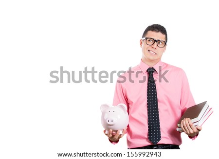 A portrait of a young student holding books in one hand and piggy bank in the other, looking thoughtful and skeptical isolated on a white background with copy space.Value and cost of education concept - stock photo