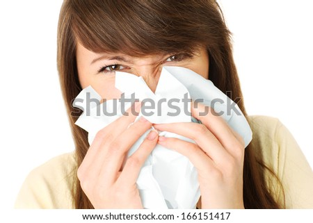 A portrait of a young woman blowing her nose over white background - stock photo