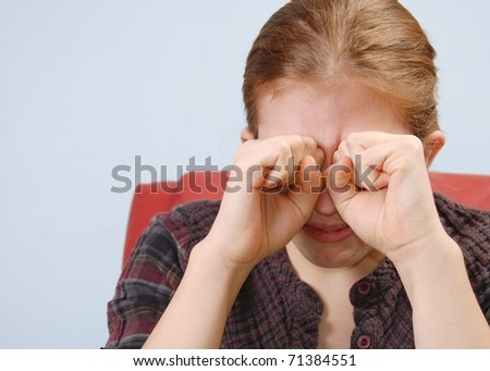 A Portrait of a Young Woman Crying with her Fists Raised to her Eyes with Room for Text - stock photo