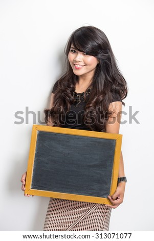 A portrait of a young woman holding a chalkboard over white background - stock photo