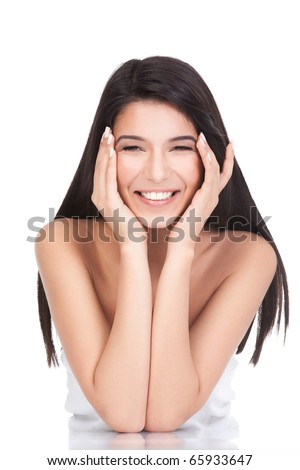 a portrait of a young woman, posing on a white background. she has both her elbows resting on a white table. both her hands are on her face, she has a wide smile and a relaxed face expression. - stock photo