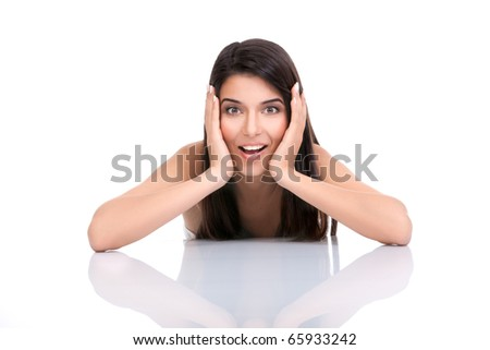 a portrait of a young woman, posing on a white background. she has her elbows on a white table and her hands on her face. she has a surprised expression on her face. - stock photo