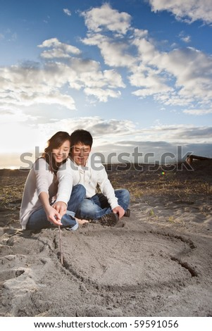 A portrait of an asian couple drawing love symbol on the sand - stock photo