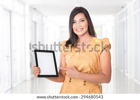 A portrait of an asian woman holding a digital touch screen tablet computer presenting - stock photo