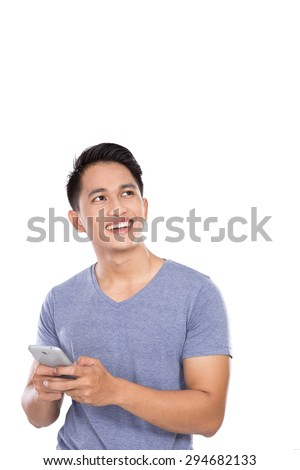 A portrait of an Asian young man holding a handphone and looking up to copyspace - stock photo