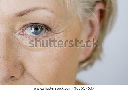 A portrait of an attractive senior woman, close-up of eye - stock photo