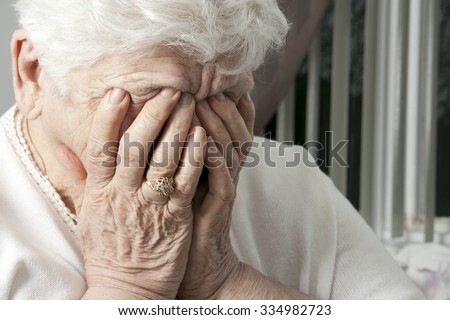 A portrait of an elderly woman having some depress problem. She have the hand on si face. - stock photo