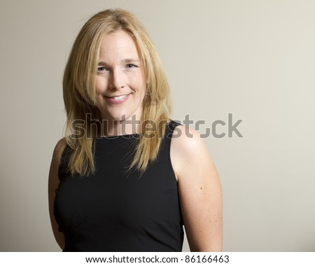 A portrait of an elegantly dressed young, attractive caucasian woman, smiling. - stock photo