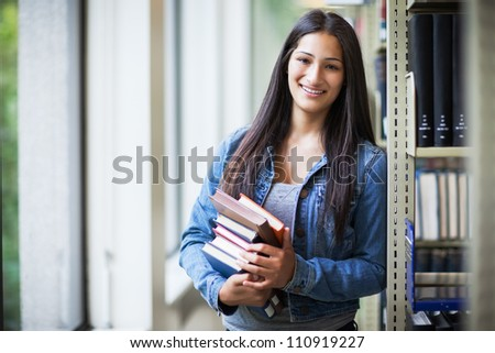 A portrait of an Hispanic college student in the library - stock photo