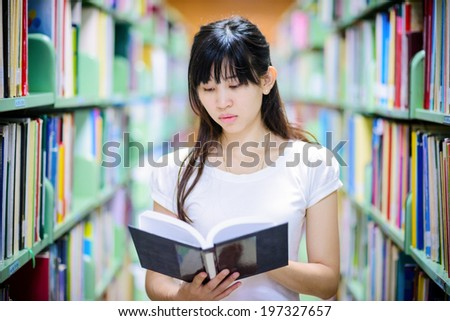 A portrait of  Asian college student  studying in the library , thai student - stock photo