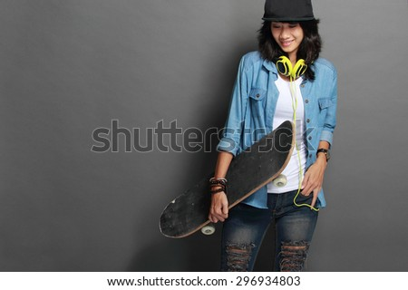 A portrait of asian young skater girl holding a skateboard over grey background - stock photo