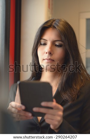 A portrait of attractive brunette woman using tablet in train, while commuting from work - stock photo