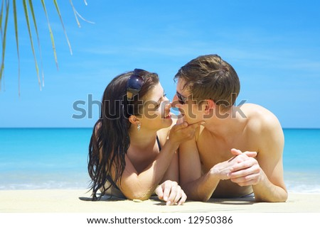 a portrait of attractive couple having chat on the beach - stock photo