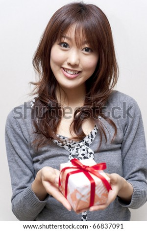 a portrait of beautiful girl holding a gift box isolated on white background - stock photo