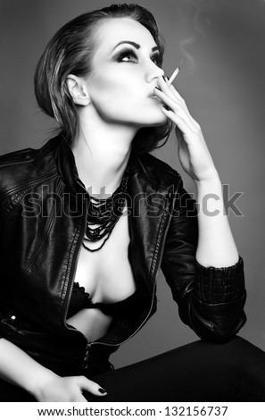 a portrait of beautiful sexual redheaded girl is in a black leather jacket, smoking a cigarette - stock photo