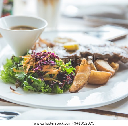 A portrait of Beef grill steak with salad and fried wedges potato, close up - stock photo