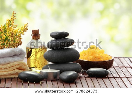 A portrait of Essential oil , candle, towel and stones for spa teraphy - stock photo