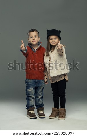 A portrait of girl and boy. Thumbs up - stock photo