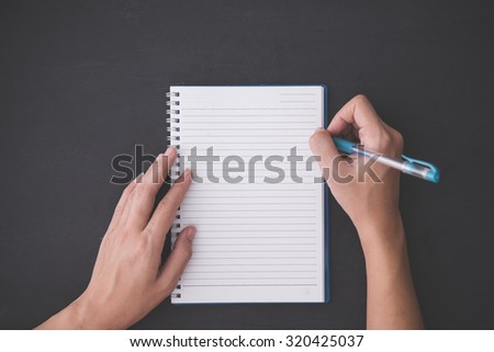 A portrait of hand holding pen, with a blank notes over blackboard background - stock photo