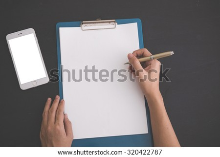 A portrait of hands writing on a clipboard, and blank white mobile phone on the side. black background. Mock up - stock photo
