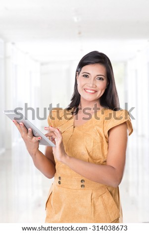 A portrait of middle aged asian woman holding a digital touch screen tablet computer - stock photo