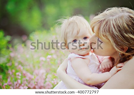 A portrait of mothers and daughters on the blooming meadow, mother kissing daughter on the cheek. - stock photo