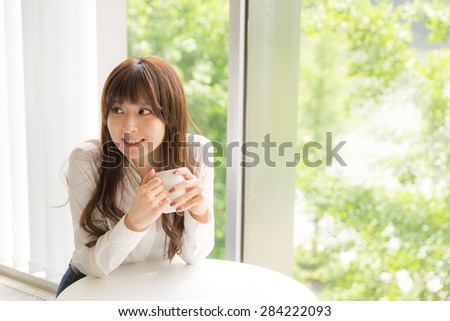 a portrait of pretty asian woman with a cup  - stock photo