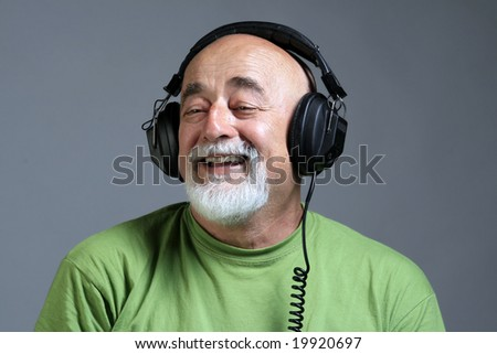 a portrait of smile old man with head phones - stock photo