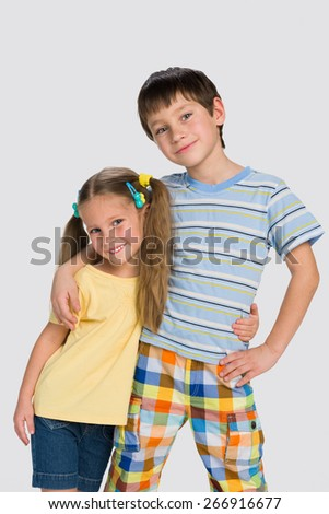 A portrait of two happy little children together on the gray background - stock photo