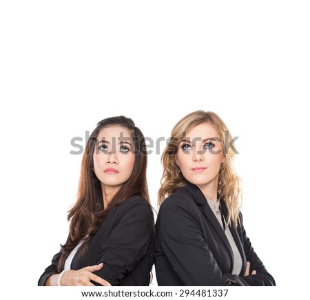 A portrait of two young businesswoman leaning against each other, looking up to copyspace isolated - stock photo