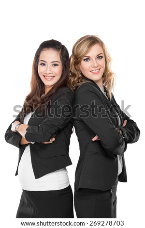 A portrait of two young businesswoman smiling while leaning against each other, isolated - stock photo