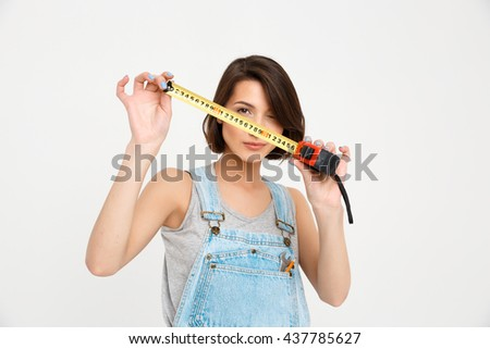 A portrait of young beautiful girl, in gray shirt and denim overall, holding tape measure, looking at camera, isolated on white background - stock photo