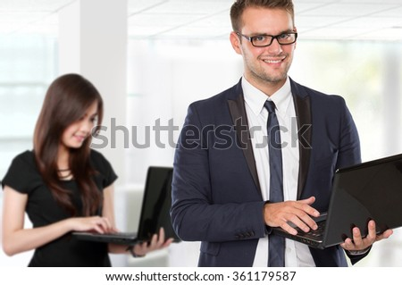 A portrait of young businessperson holding laptop and businesswoman at the background - stock photo