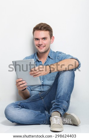 A portrait of young caucasian man sitting on the floor holding a tablet pc - stock photo