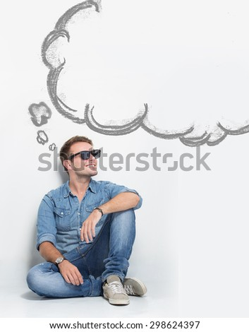 A portrait of young caucasian man wear sunglasses while sitting on the floor thinking about something. copyspace with bubble speech - stock photo