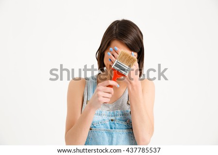 A portrait of young pretty girl, in gray shirt and denim overall, hiding face, holding painting brush, isolated on white background - stock photo