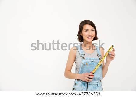 A portrait of young smiling beautiful girl, in gray shirt and denim overall, holding tape measure, looking at camera, isolated on white background - stock photo