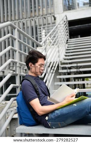 A portrait of young student holding book sitting at campus - stock photo