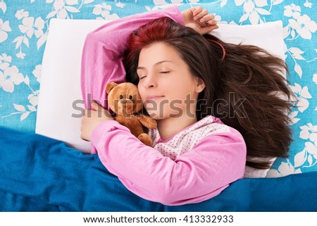 A portrait shot of a young girl sleeping and hugging her bear. - stock photo