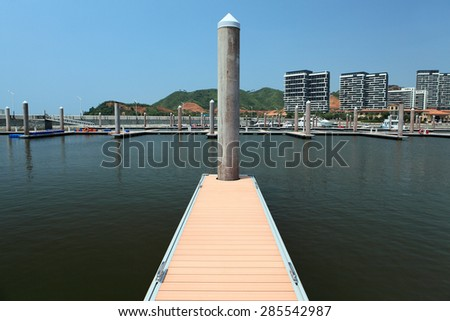 a position piling pointing upward with footpath on a pier head with mooring cleats and berth of yacht marina on pontoons - stock photo