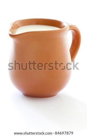 A pottery pitcher of milk on white background - stock photo