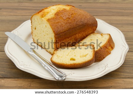 A pound cake and a knife on a white plate. A wooden table. Breakfast time. - stock photo