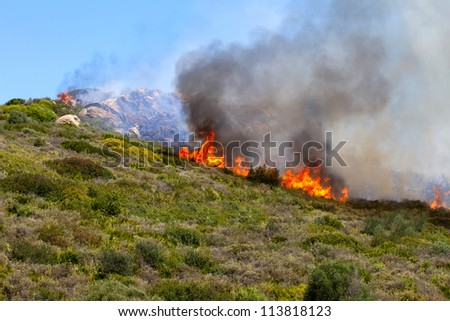 a powerful fire spreads through the hillside - stock photo